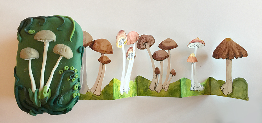 A mint tin covered in polymer clay decorated with realistic looking mushrooms holds a concertina-style row of water color mushrooms.